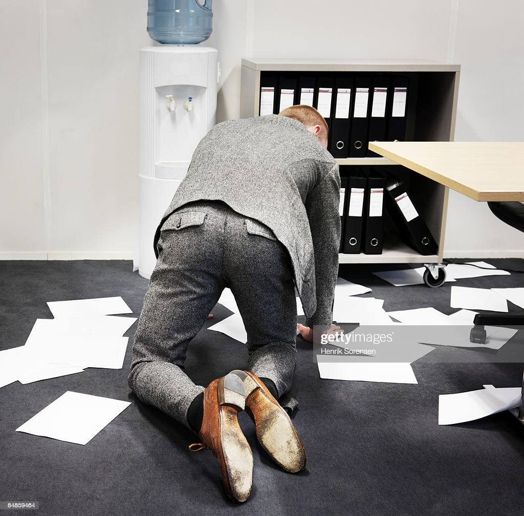 Man picking up papers from the office floor.