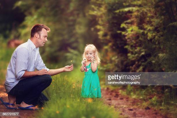 Man picking wild flowers with a little girl