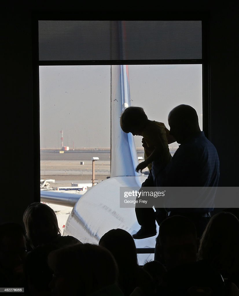 A man picks up a child as they wait to board a plane the Salt Lake City international Airport on November 27, 2013 in Salt Lake City, Utah. A wintry storm system that is covering much of the nation is threatening to wreak havoc on holiday travel .