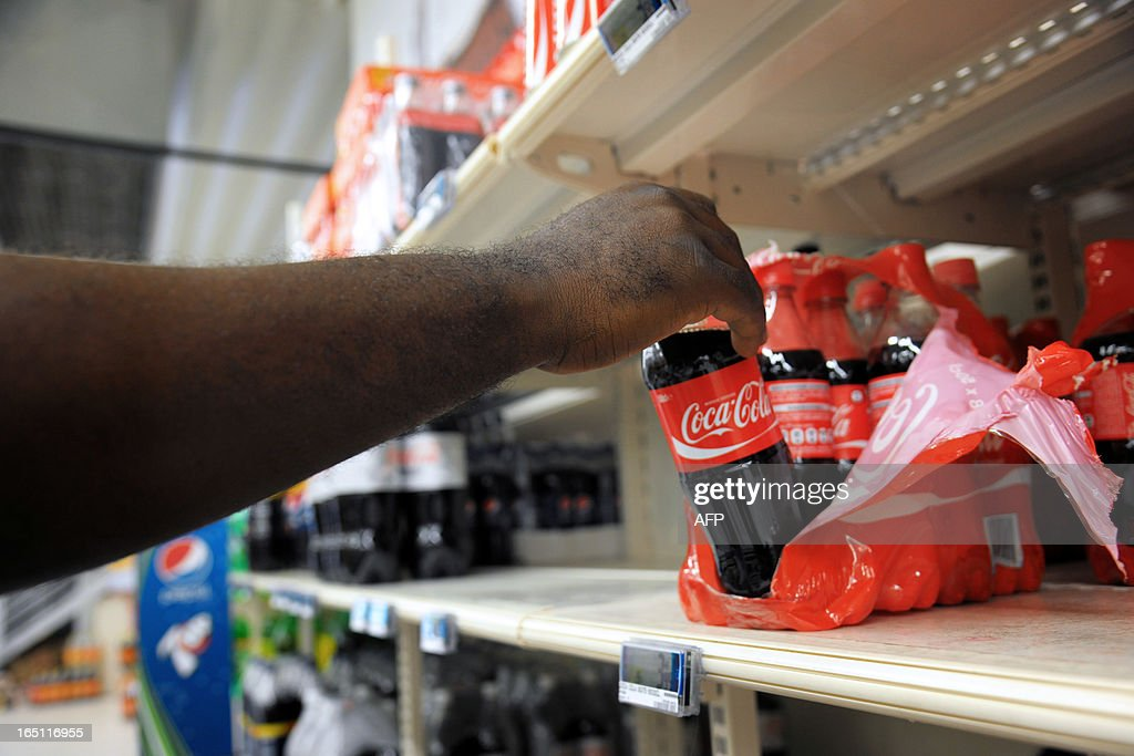 A man picks up a Coca Cola bottle in a supermarket of Fort-de-France, on March 30, 2013 in the French caribean island of La Martinique. The French national assembly on March 27, 2013 ruled to align the additional sugar rates of the products sale in the overseas territories with the mainland's rates. AFP PHOTO JEAN-MICHEL ANDRE
