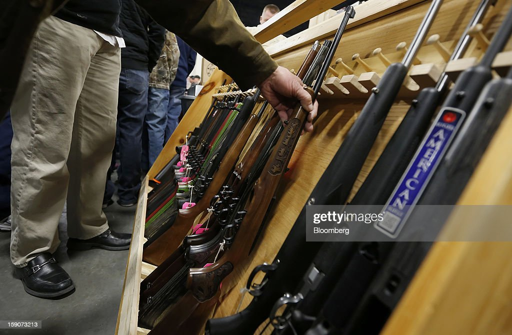A man picks up a long rifle at the Rocky Mountain Gun Show in Sandy, Utah, U.S., on Saturday, Jan. 5, 2013. A working group led by Vice President Joe Biden is seriously considering measures that would require universal background checks for firearm buyers, track the movement and sale of weapons through a national database, strengthen mental health checks and stiffen penalties for carrying guns near schools or giving them to minors. Photographer: George Frey/Bloomberg via Getty Images