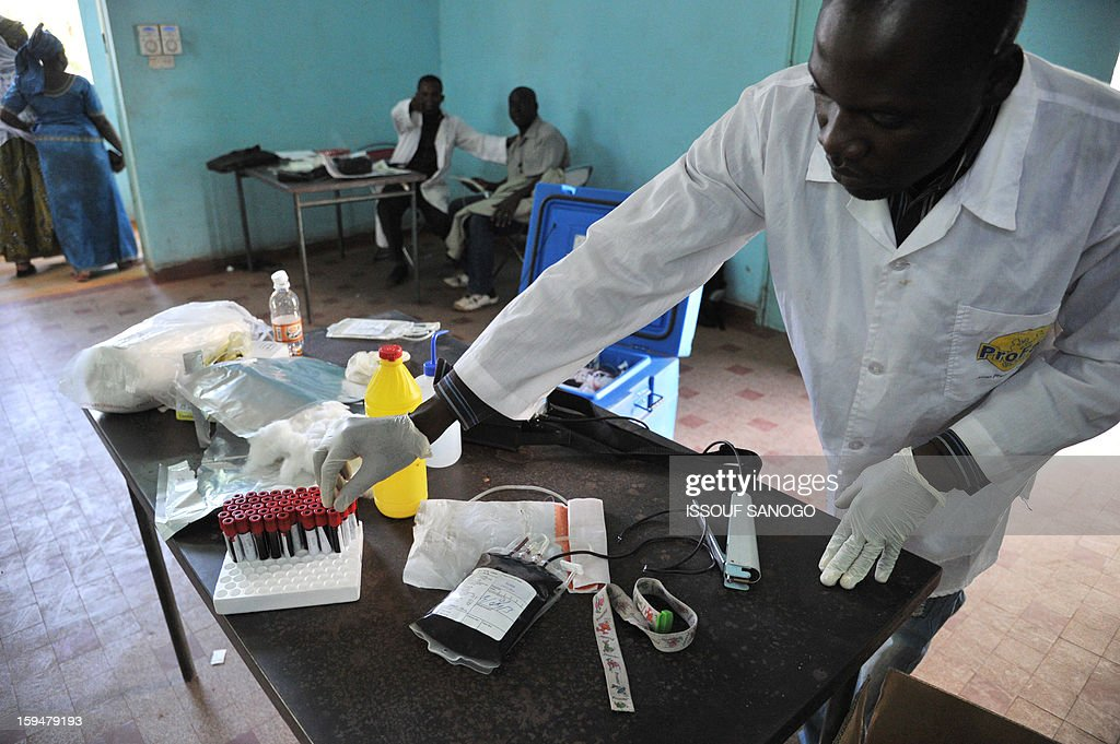 A man picks up a test tube during a blood donation, on January 14, 2013 in Bamako. Islamists have retreated in the east of Mali but French forces are facing a difficult situation in the west of the country where rebels are well armed, French Defence Minister Jean-Yves Le Drian said on January 14. France launched the operation alongside the Malian army on January 11, 2013 to counter a push south by the insurgents who had threatened to advance on the capital Bamako.