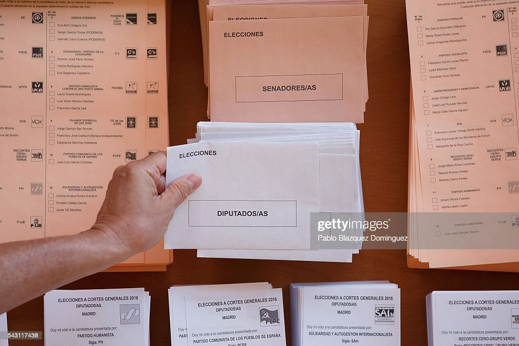 A man picks up an envelope to cast his vote during the Spanish General Elections on June 26, 2016 in Madrid, Spain. Spanish voters head back to the polls after the last election in December failed to produce a government. Latest opinion polls suggest the Unidos Podemos left-wing alliance could make enough gains to come in second behind the ruling center right Popular Party.