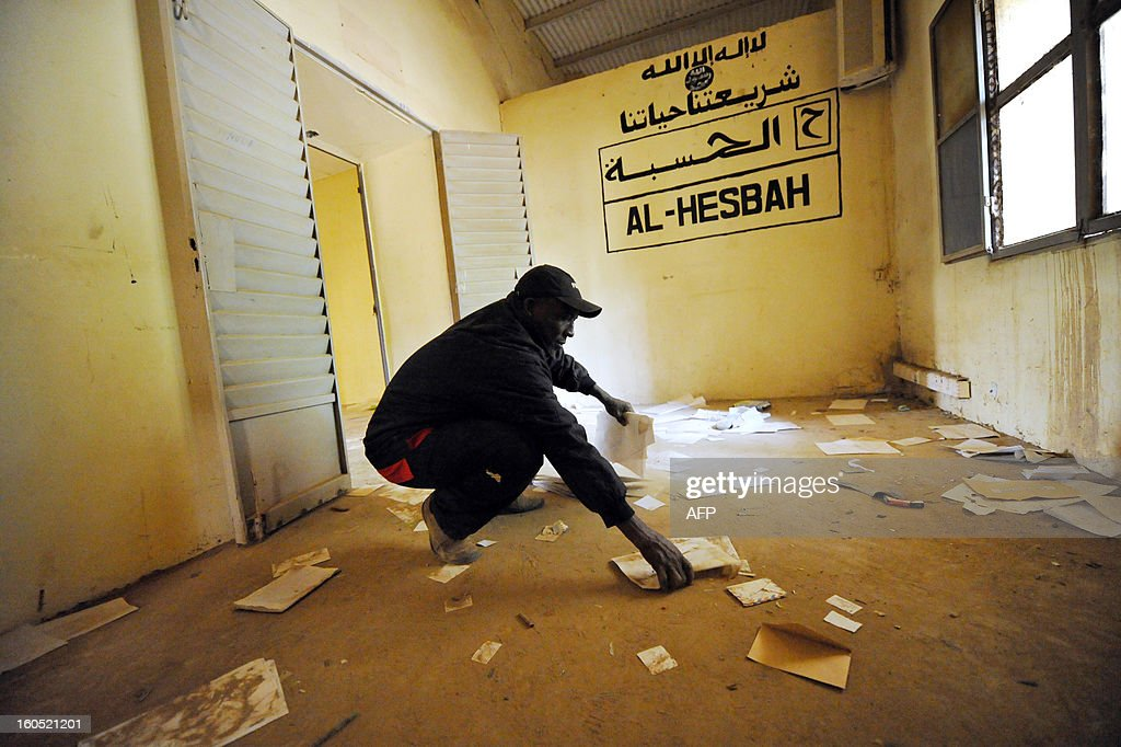 A man picks up birth certificates, on February 1, 2013, in the Gao town hall looted by former Islamist occupiers. President Francois Hollande visits Mali on February 2, as French-led troops worked to secure the last Islamist stronghold in the north after a lightning offensive against the extremists. Gao's light-skinned Arab and Tuareg residents face the violent anger of their black neighbours since French and Malian troops reclaimed the city from the rebels of the Movement for Oneness and Jihad in West Africa (MUJAO) on January 26.