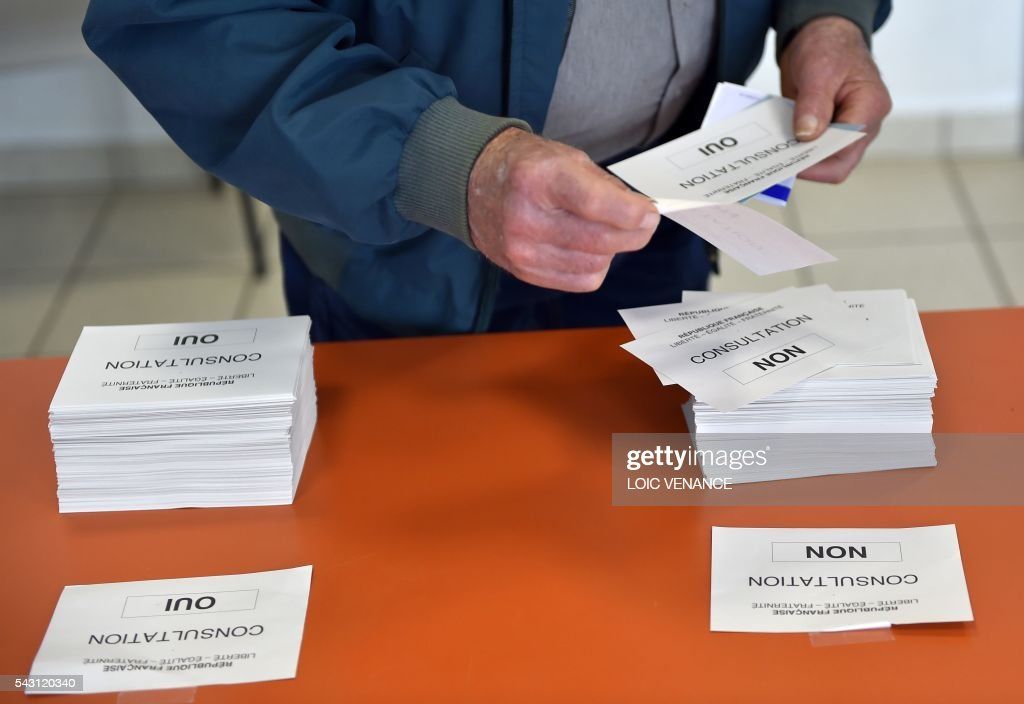 A man picks up his ballot paper before casting his vote on June 26, 2016, in Notre-Dame-des-Landes during a local referendum organised in Loire-Atlantique on subject of the Notre-Dame-des-Landes' airport project. Nearly One million people living in France's Loire-Atlantique department are voting in a referendum which poses the question 'Are you in favour of the project to transfer the Nantes-Atlantique airport to the municipality of de Notre-Dame-des-Landes?' to voters. The referendum was organised by the French executive power hoping to find a solution to the issue which has dragged on for 50 years. / AFP / LOIC