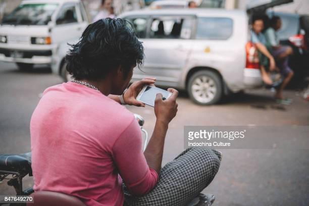 Man (Burmese using phone -rear view)