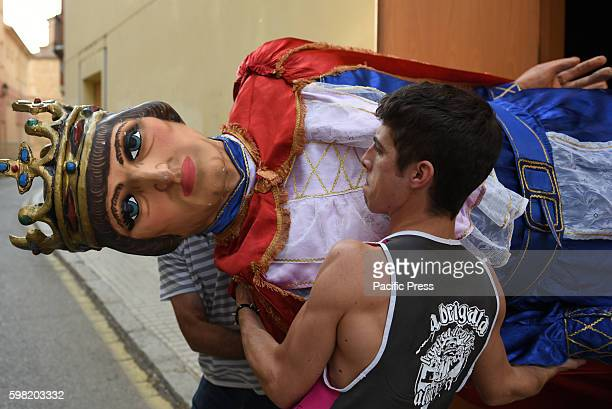 A man pictured carrying a costume figure Gigante during the 'La Bajada de Jesús' festival in Almazán north of Spain