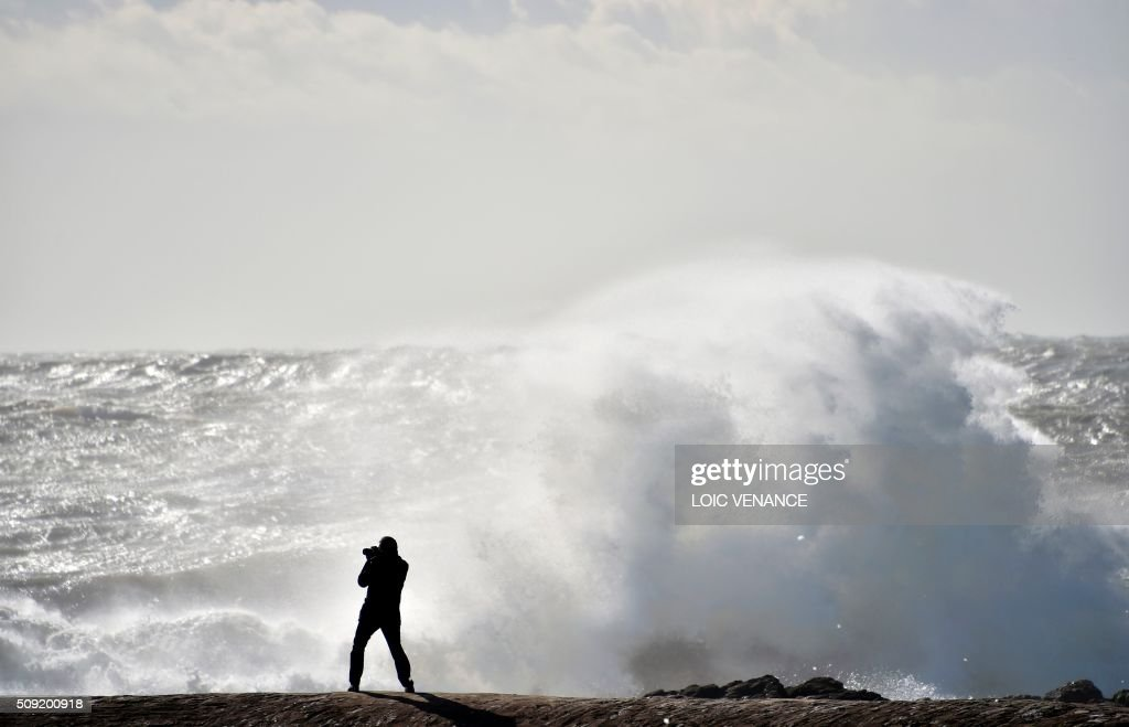 A man pictures a wave breaking against a breakwater in Les Sables-d'Olonne, western France, on February 9, 2016. High winds buffeted northwestern Europe on February 8, leaving one woman in France in a coma after she was hit by an advertising hoarding. Electricity was cut to 5,000 homes in northern France. / AFP / LOIC VENANCE