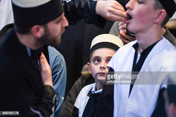 TOPSHOT A man pierces the cheeks of a Kosovo dervish young man with needles during a ceremony in the prayer room in the town of Prizren on March 22...