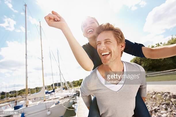 A man piggy backing a woman having a lot of fun