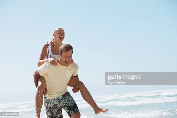 Man piggybacking woman on beach