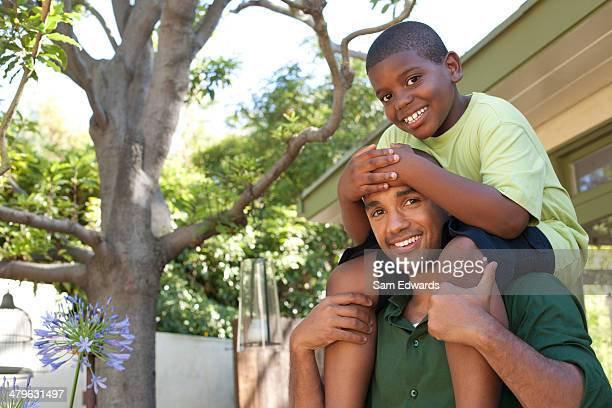 Man piggybacking young boy in back yard
