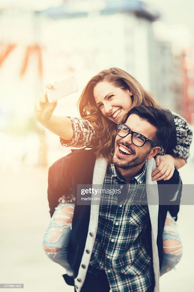 Homme piggybacks fille pour un selfie : Photo