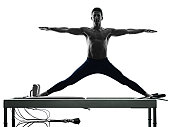 one caucasian man exercising pilates reformer exercises fitness in silhouette isolated on white backgound