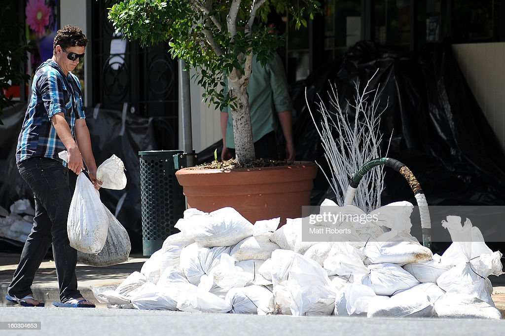 A man place sandbags out front of the shops in the inner city suburb of Rosalie prior to today's high tide as parts of southern Queensland experiences record flooding in the wake of Tropical Cyclone Oswald on January 29, 2013 in Brisbane, Australia. The river in the Brisbane CBD is expected to peak at 2.3 metres today - lower than the 2.6 metre peak predicted - but is still likely to flood low-lying properties and businesses. The flood crisis has claimed four lives so far, with the city of Bundaberg, Queensland faces the worst flooding in its history.