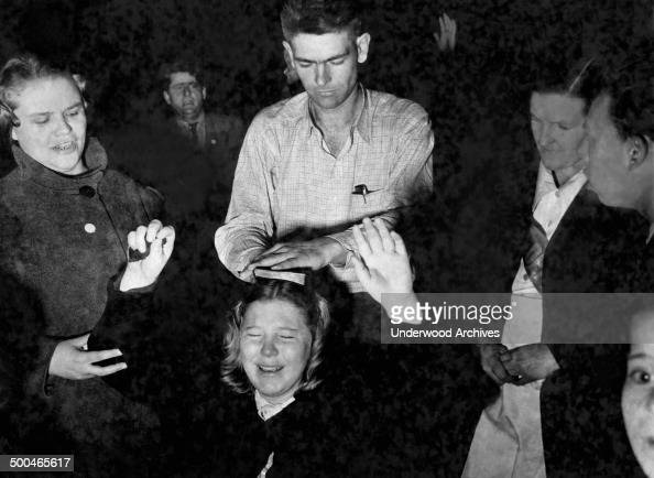 A man places a bible on the head of an ecstatic kneeling worshipper responding to the call of the preacher at a religious tent revival meeting circa...