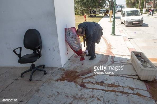A man places a bouquet on the crime scene outside the National Bardo Museum in Tunis on March 19 2015 after the attack at museum At least 23 people...
