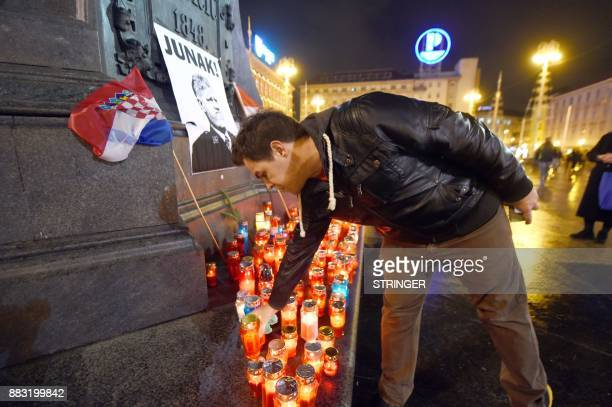 A man places a candle in tribute to General Slobodan Praljak in Zagreb on November 30 after the Bosnian Croat war criminal took his own life in front...