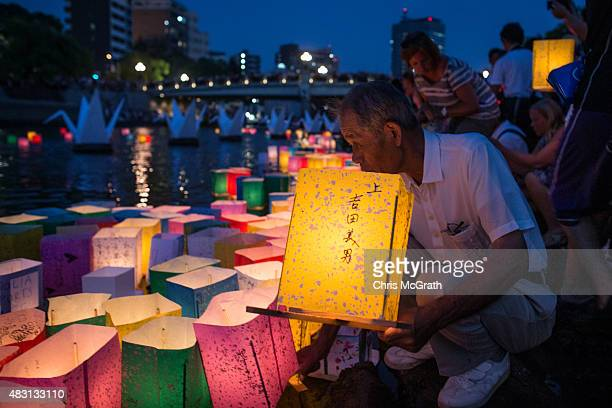A man places a candle lit paper lantern on the river during 70th anniversary activities commemorating the atomic bombing of Hiroshima at the...