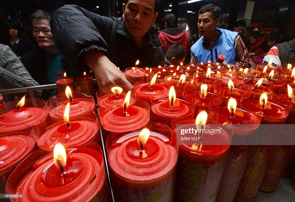 A man places a candle on a table for good fortune at Hongludi temple, a Taoist god of fortune, in Chunghe, the New Taipei City, on the third day of the lunar new year on February 12, 2013. Chinese lunar new year, celebrated by Chinese communities the world over, falls on February 10 with the beginning of the new moon. AFP PHOTO / Sam Yeh