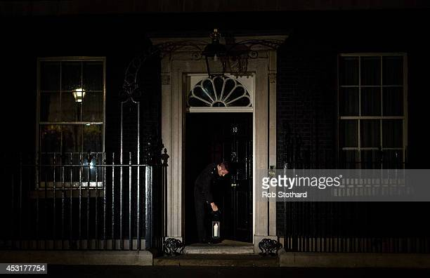 A man places a candle on the doorstep of number 10 Downing Street as the lights are turned off on iconic buildings as the city marks the centenary of...