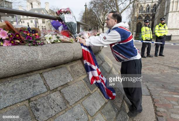 A man places a floral tribute near a police cordon in Westminster in central London on March 23 2017 a day after a deadly terror attack killed at...