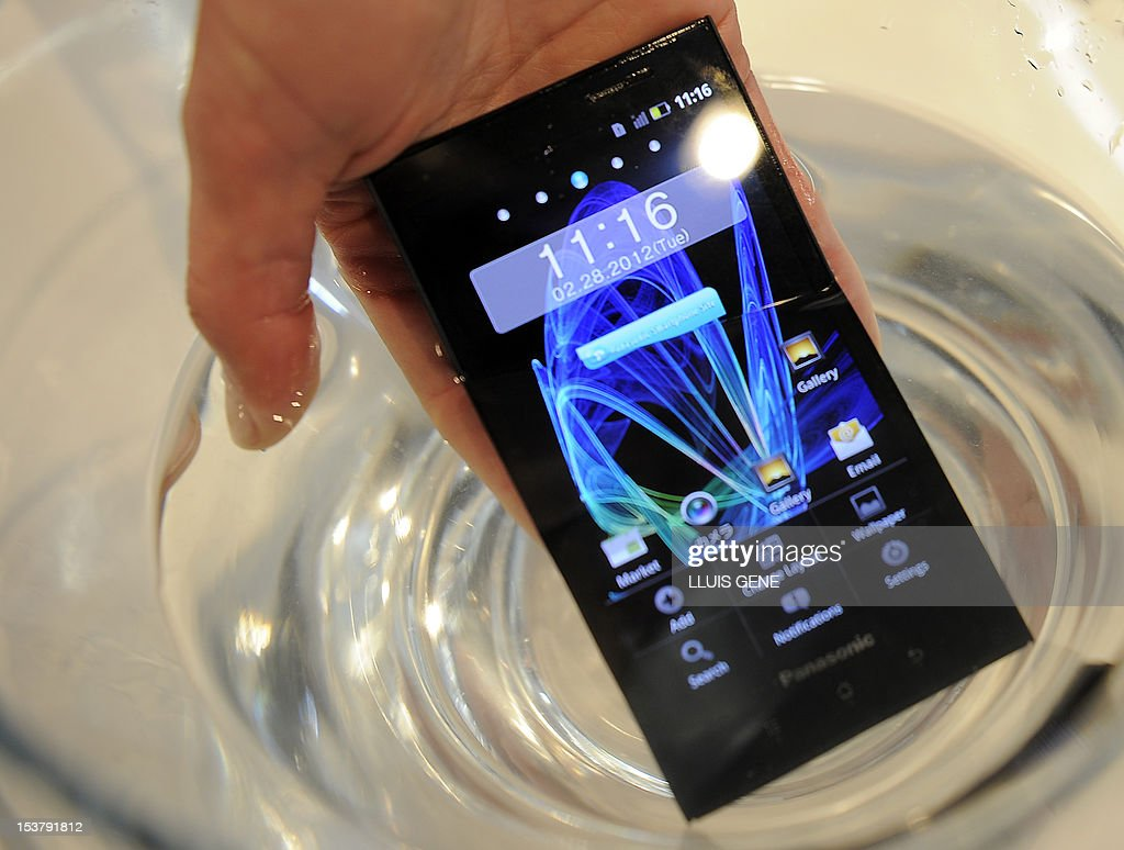 A man places a Panasonic Eluga Power waterproof smartphone on a glass of water during a presentation at the Mobile World Congress on February 28, 2012 in Barcelona. The 2012 Mobile World Congress, the world's biggest mobile fair, is held from February 27 to March 1 in Barcelona. AFP PHOTO/LLUIS GENE