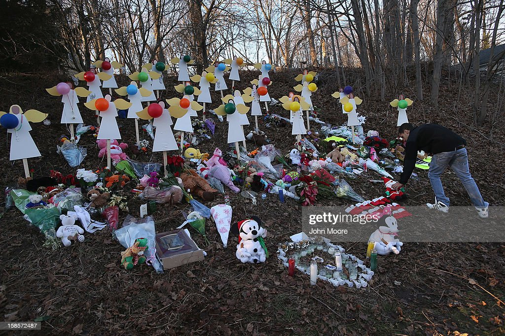 A man places a plush santa at a makeshift memorial for Sandy Hook shooting victims on December 19, 2012 in Newtown, Connecticut. Adam Lanza reportedly shot his mother Nancy Lanza last Friday before he killed 26 others, including 20 children, at Sandy Hook Elementary School.