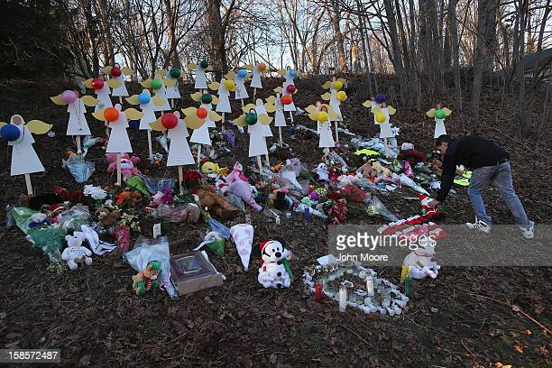 A man places a plush santa at a makeshift memorial for Sandy Hook shooting victims on December 19 2012 in Newtown Connecticut Adam Lanza reportedly...