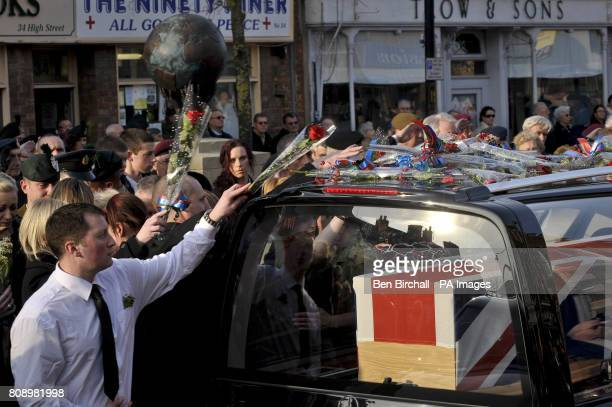 A man places a single red rose on top of the hearse containing the Union Flag draped coffin of Corporal Stephen McKee of the Royal Irish Regiment as...