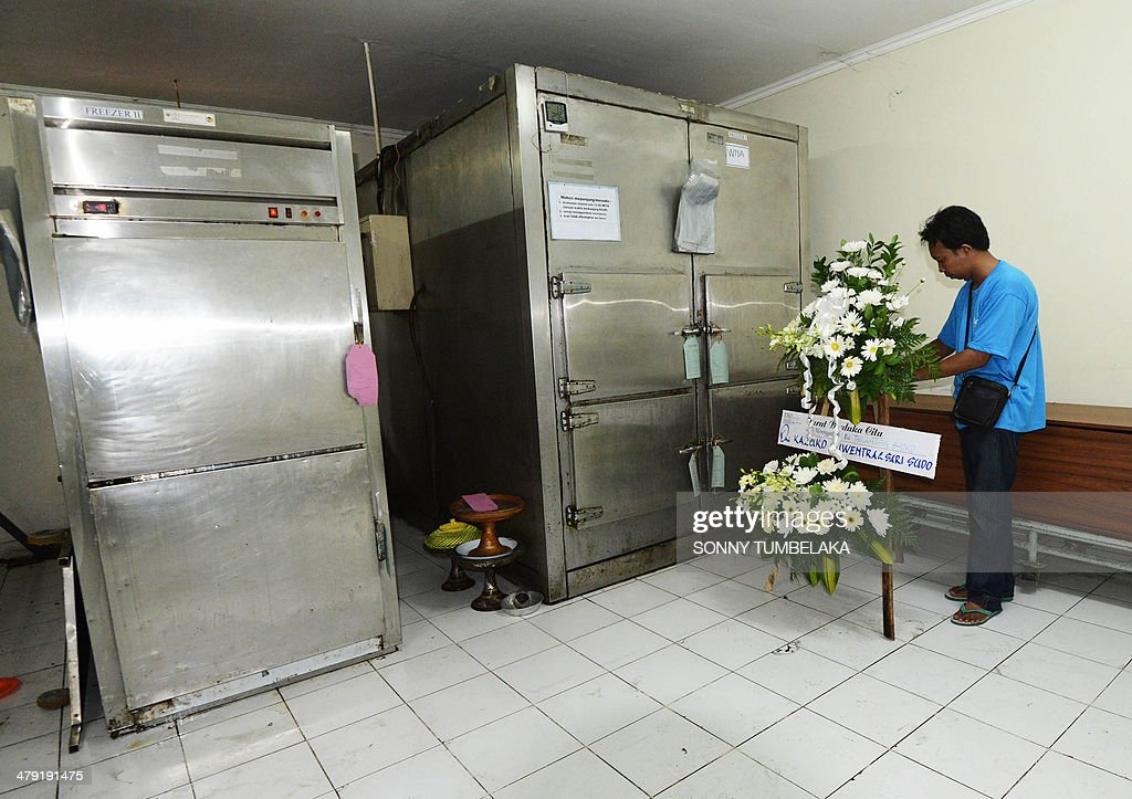 A man places a wreath for the body thought to be that of diving instructor Shoko Takahashi at a mortuary room in Sanglah hospital in Denpasar Bali...