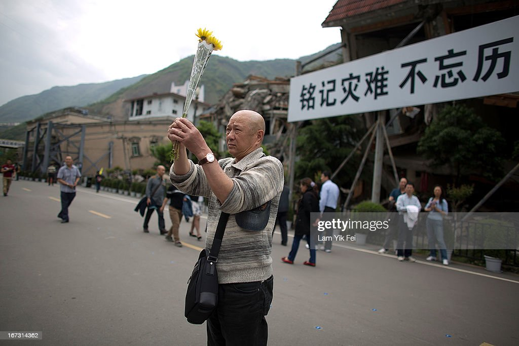A man places flowers ans mourns for the victims of the earthquake at a park at the Beichuan town in Sichuan province on April 24, 2013 in Chengdu, China. The Beichuan earthquake memorial was built in memory of the over 70,000 that perished in the deadly 2008 quake that struck Sichuan province and was built near the Beichuan Middle School, where over 1,000 students and teachers died. With the five year quake anniversary only a few weeks away, residents of Sichuan province are coming to grips with the April 20 earthquake in nearby Ya'An that claimed the lives of over 190 people and injured thousands.