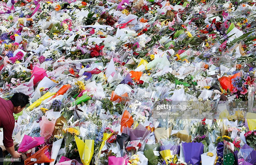 A man places flowers as a mark of respect for the victims of Martin Place siege on December 16 2014 in Sydney Australia Sydney siege gunman Man Haron...