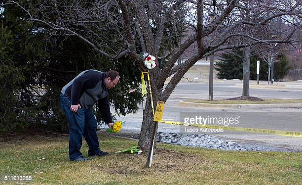 A man places flowers at a Cracker Barrel where a gunman went on a shooting rampage on February 21 2016 in Kalamazoo Michigan Authorities said that a...