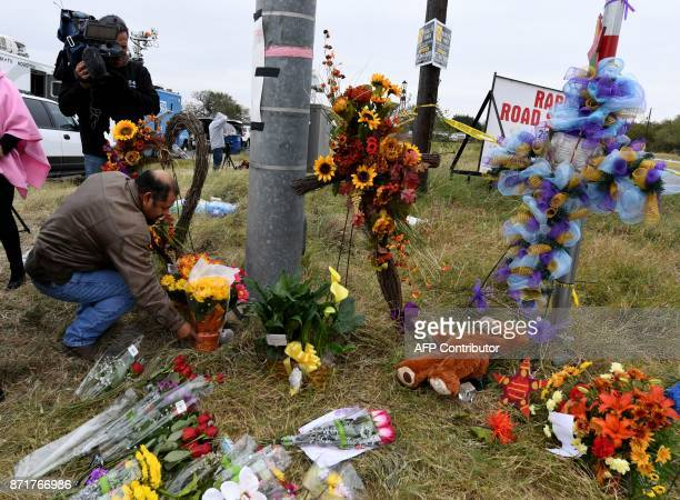 A man places flowers at a memorial outside the First Baptist Church which was the scene of the mass shooting that killed 26 people in Sutherland...