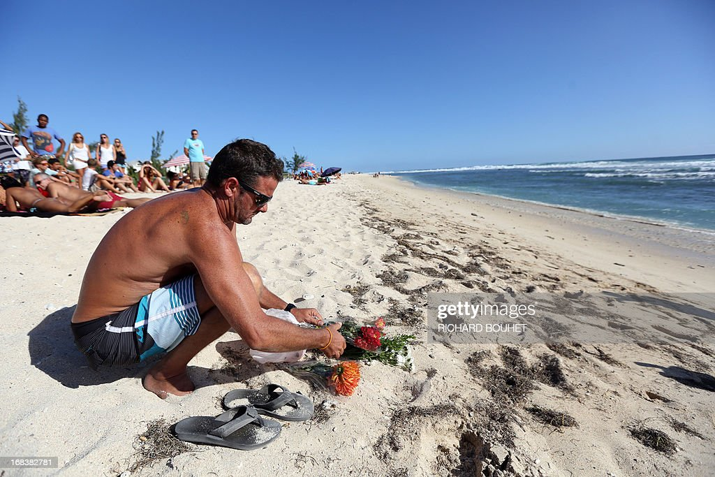 A man places flowers in the sand on the beach of Brisants in Saint-Gilles-les Bains on May 9, 2013 to pay tribute to a surfer killed after he was attacked by a shark on May 8. The 36-year-old French honeymooner was in the sea off the popular beach of Brisants de Saint-Gilles when a shark charged at him twice, prompting a nearby swimmer to raise the alert when he saw blood on the water, the local prefecture said.