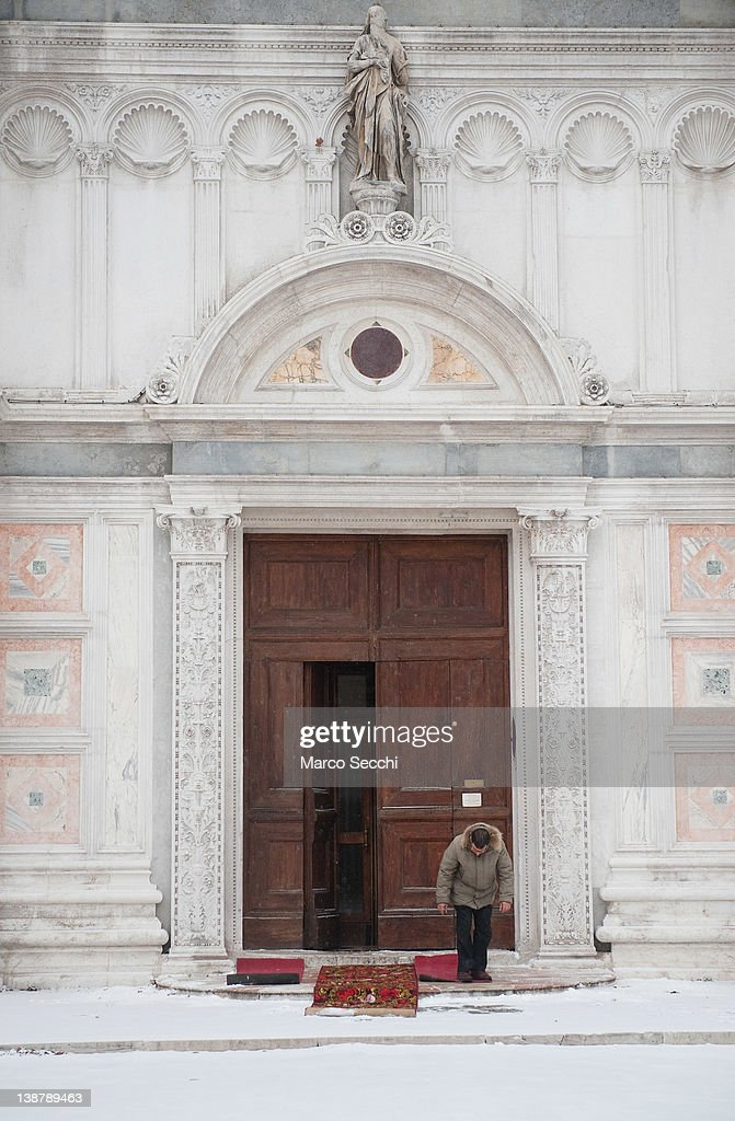 A man places old carpets in front of a church steps to avoid falls due to ice and snow on February 12, 2012 in Venice, Italy. Italy, like most of Europe, is experiencing freezing temperatures, with the Venice Lagoon freeezing for the first time in over 20 years.