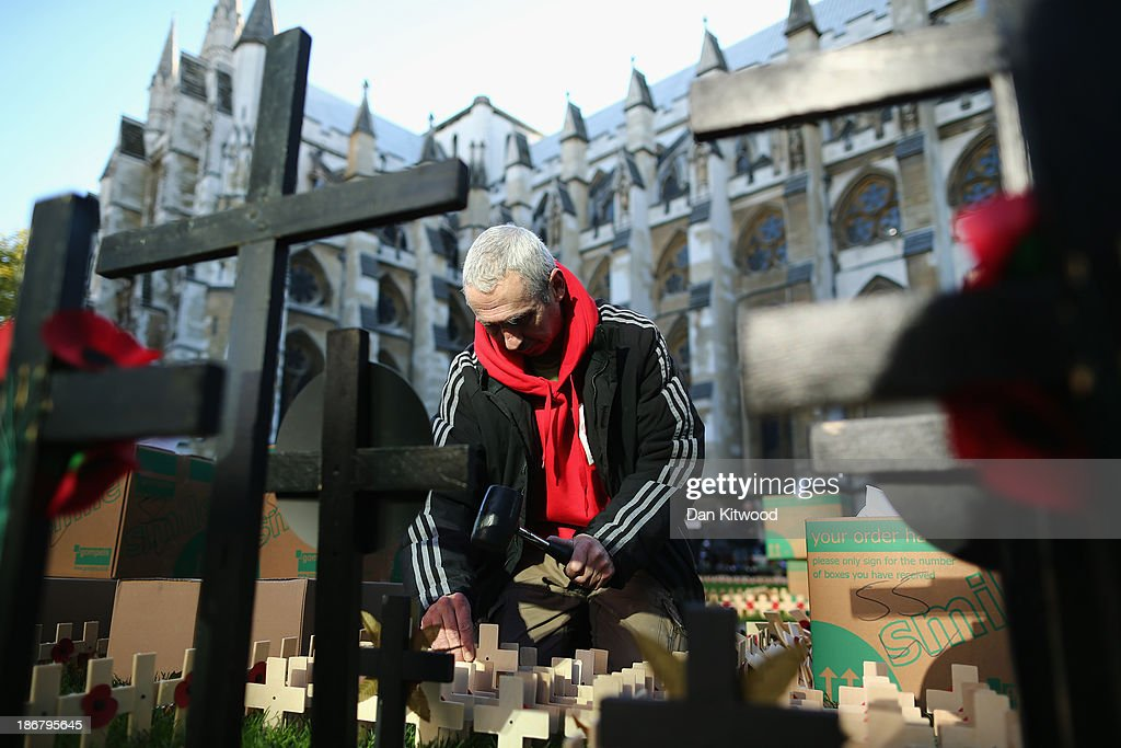 A man places remembrance crosses outside Westminster Abbey ahead of the official opening of the Royal British Legion's Field of Remembrance on November 4, 2013 in London, England. Hundreds of small crosses bearing a poppy have been planted in the Field of Remembrance to pay tribute to British servicemen and women who have lost their lives in conflict.