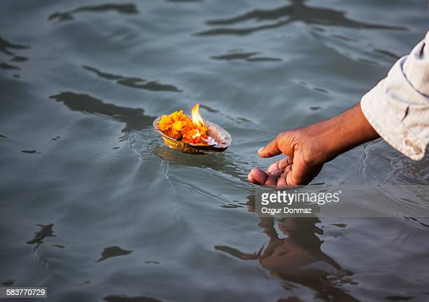 Man placing a candle offering into River Ganges