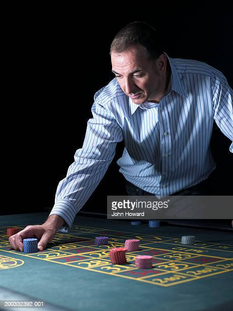 Man placing chips on number at roulette table