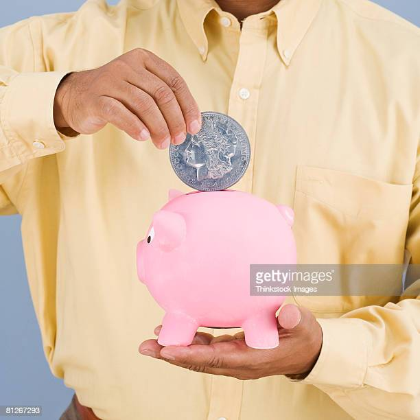 Man placing large coin in piggy bank