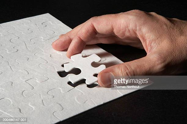 Man placing last piece in jigsaw puzzle, close-up of hand