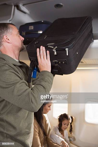 Man placing luggage in overhead compartment on airplane
