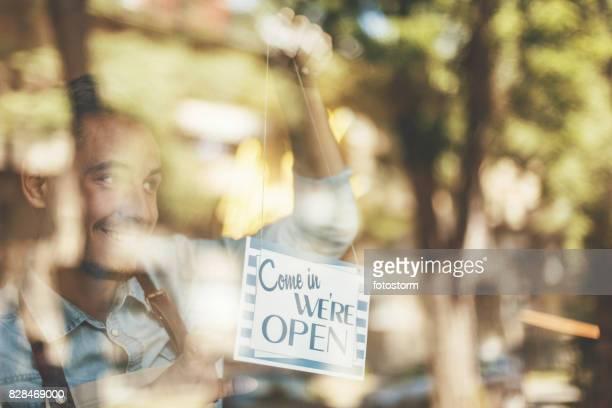 Mann Platzierung offenen Schild an Café Tür
