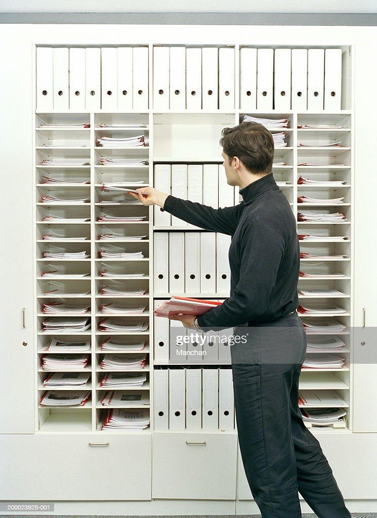 Man placing paperwork in pigeonholes
