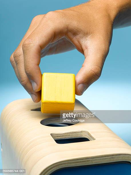 Man placing square peg in round hole