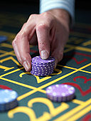 Man placing stack of chips on number at roulette table, close-up