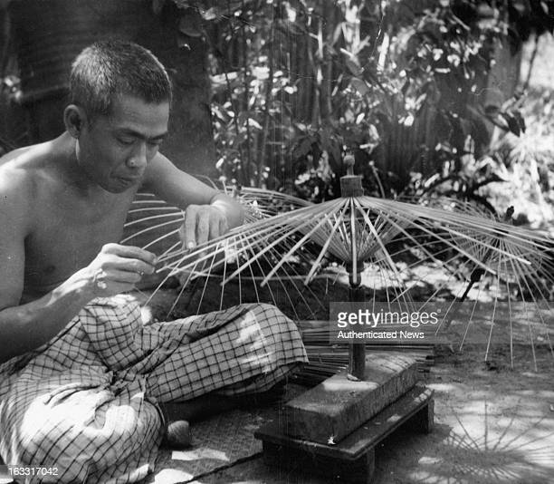 Man placing the spokes of an umbrella in position in Burma 1955