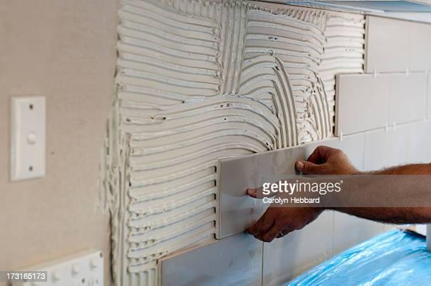 Man placing tile on wall