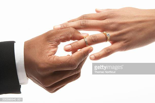 Man placing wedding ring on woman's finger, close-up
